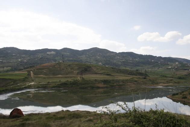Rostige Förderanlagen spielgen sich in einem kleinen See.