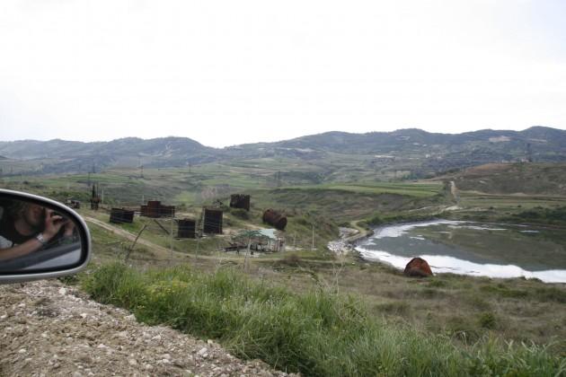 Abfälle der alten Förderindustrie liegen in der Landschaft herum.